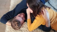 Couple lying down on rug in new home