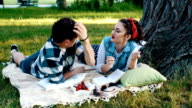 Couple lying on a blanket and feed each other with a cherry