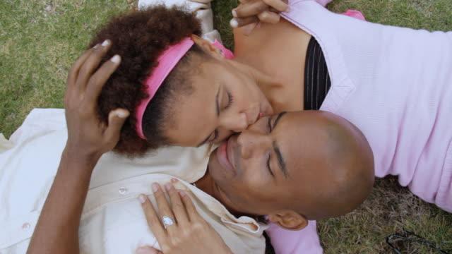 CU Couple lying on grass kissing each other / Havana, Cuba