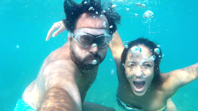 Couple making faces and waving underwater