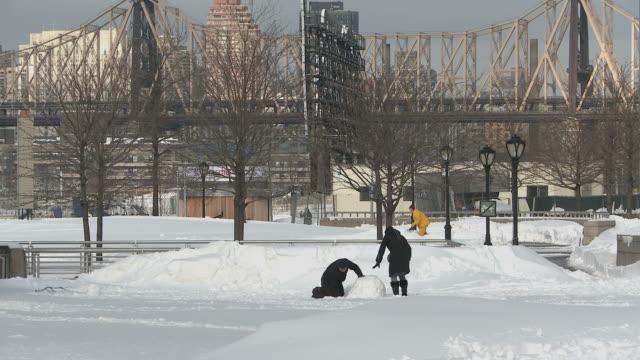 WS Couple making snowman / New York City, New York, USA