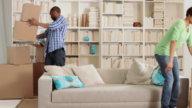 Couple moving boxes and sitting on sofa