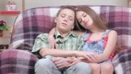Couple of teenagers: boy and girl falling asleep together indoors.