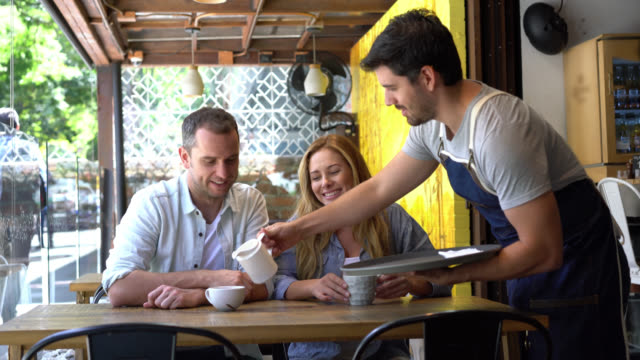 Couple on a date at a coffee shop and friendly waiter serving them