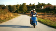 Couple on a scooter bike driving through countryside.