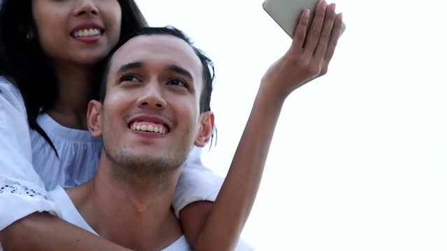 Couple on beach taking selfie photo on Hawaii with smart phone. Young woman and man in love using smartphone on beach vacations
