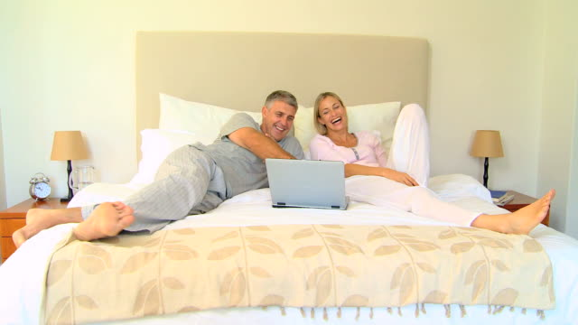 Couple on bed enjoying something hilarious on laptop / Cape Town, Western Cape, South Africa