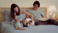 CU, ZO, MS, Couple on bed, woman stroking Bulldog