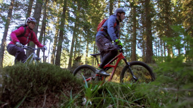 SLO MO Couple on mountain bikes riding up the forest trail