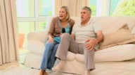 Couple on sofa ecstatic as they watch a programme on TV / Cape Town, Western Cape, South Africa