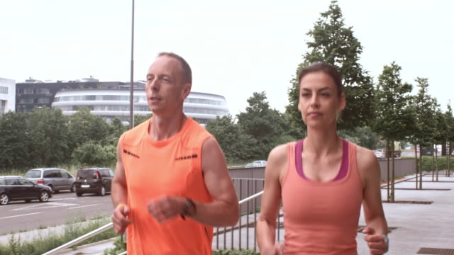 SLO MO TS Couple on their morning run through city