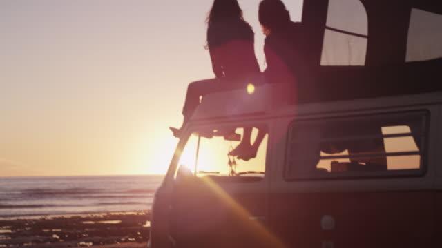 Couple on van roof, scenic beach sunset
