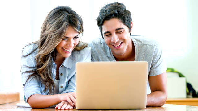 Couple online on a laptop at home