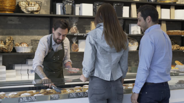 Couple ordering from the bakery counter and salesman serving