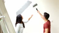Couple painting wall with paint roller and kissing