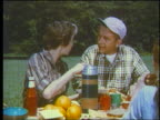 1960 couple passing food at picnic table