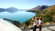 Couple pause beside camper van above lake, mtn