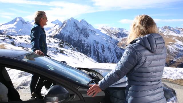 Couple pause beside car door, mountain pass summit