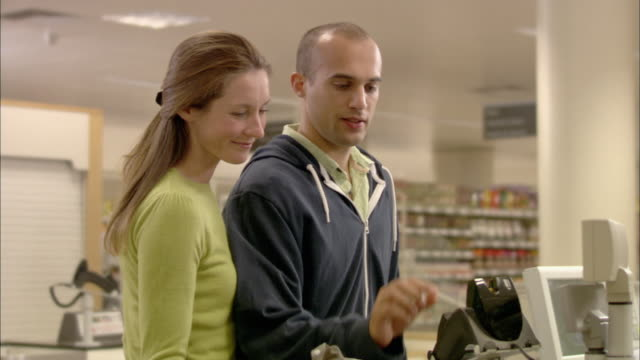 MS Couple paying at checkout with credit card and receiving receipt from cashier, walking away / North Finchley, London, UK