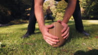 Couple playing American football in field