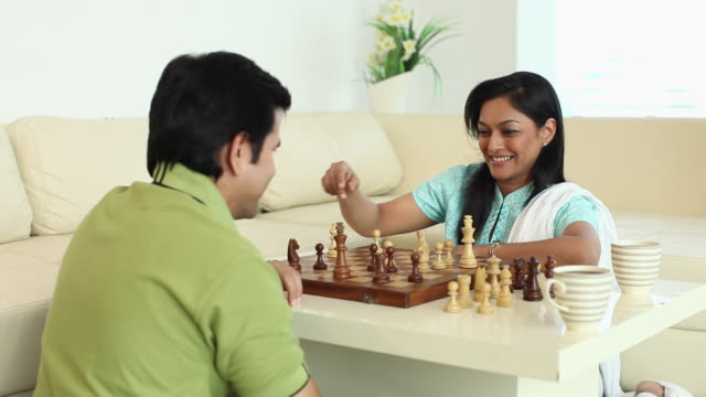 Couple playing chess in the home
