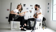 Couple playing guitars together