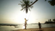 Couple playing with a swing on the beach