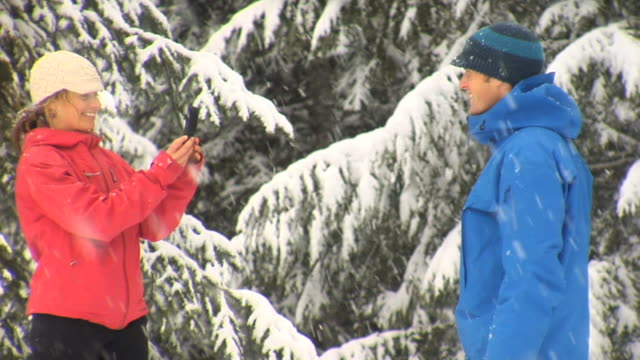 SLO MO MS Couple playing with camera in winter, Whistler, British Columbia, Canada