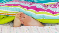 Couple playing with feet under covers in bed