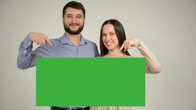 Couple pointing on copy space