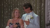 A couple poses for a picture at the prom.