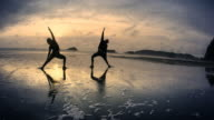 Couple practicing Yoga on Beach at Sunset
