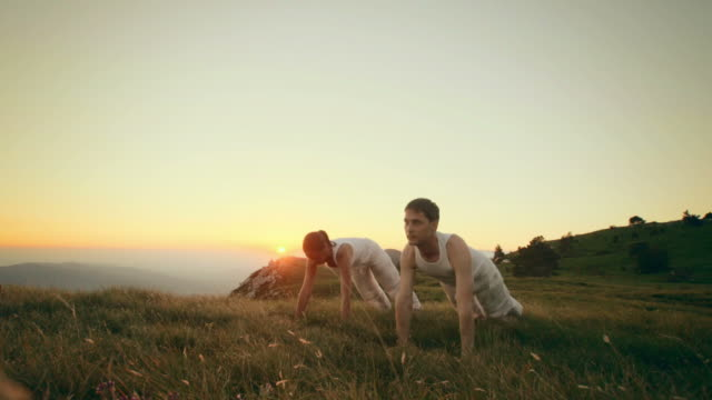 HD: Couple Practicing Yoga Outdoors At Dusk