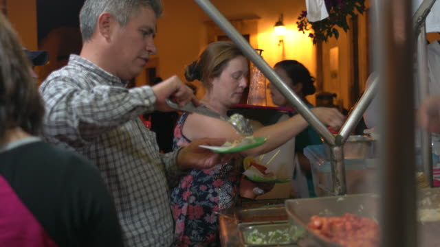 Couple prepares tacos at outdoor taco stand