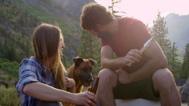 MS Couple preparing dinner at campsite woman petting dog