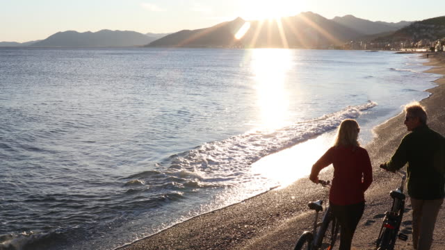 Couple push bikes along beach, look out to sea