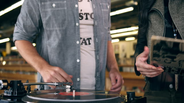 A couple puts a record on while shopping inside a record store.