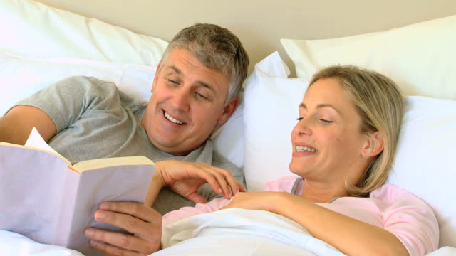 Couple reading a book in bed / Cape Town, Western Cape, South Africa