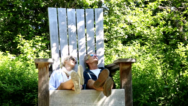 Couple relax in huge wooden chair, in forest