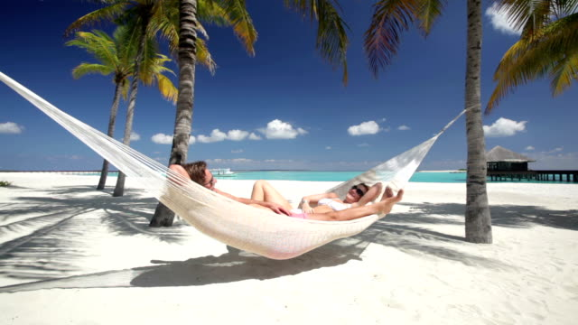 couple relaxing in hammock on tropical beach