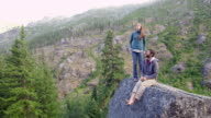 MS Couple relaxing on boulder at wilderness lookout enjoying view at sunset