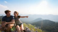 Couple resting on mountain top
