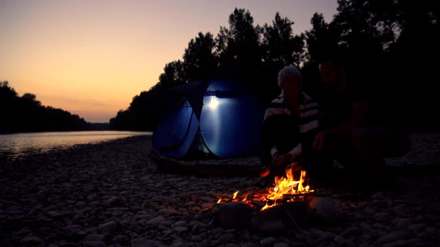 HD SUPER SLOW-MO: Couple Roasting Meat On A Campfire