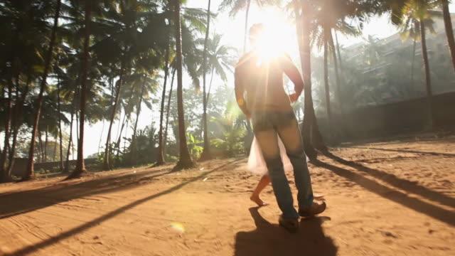 Couple romancing among palm trees