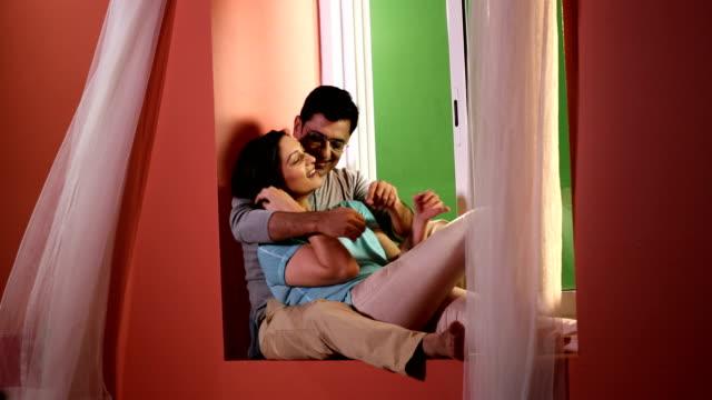Couple romancing at windowsill, Delhi, India