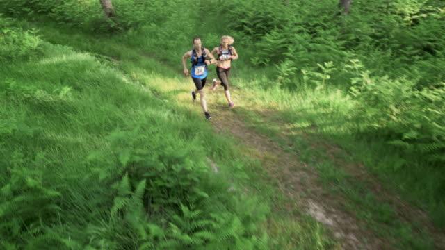 AERIAL Couple running a trail marathon through the forest