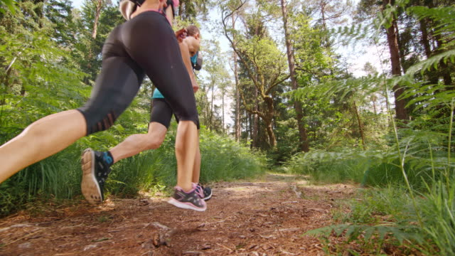 SLO MO DS Couple running across a forest clearing