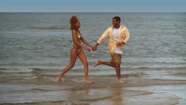 MS PAN Couple running along beach in shallow water, man picking up woman and spinning her around, Eastville, Virginia, USA