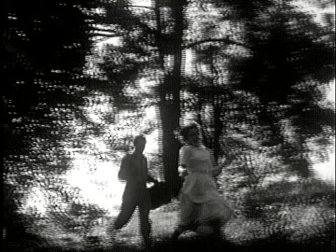 MS, B/W, LA, PAN, Couple running in forest, USA