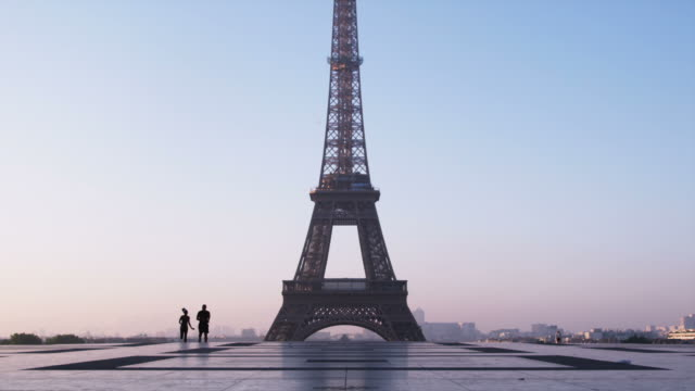 couple running in front of the Eiffel tower
